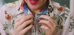 Close-up of a woman buttoning her shirt up.