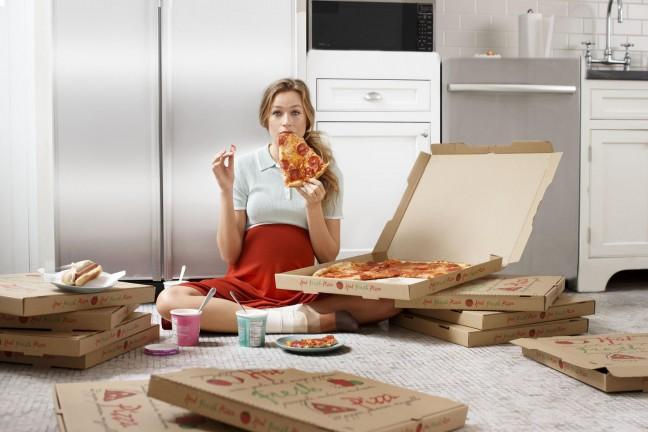 kobieta w ciąży je pizze