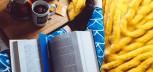 Książka leżąca na nogach czytającej kobiety