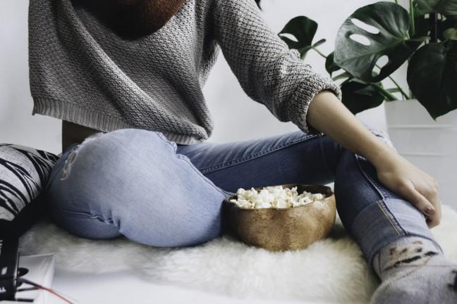 Kobieta jedząca popcorn.