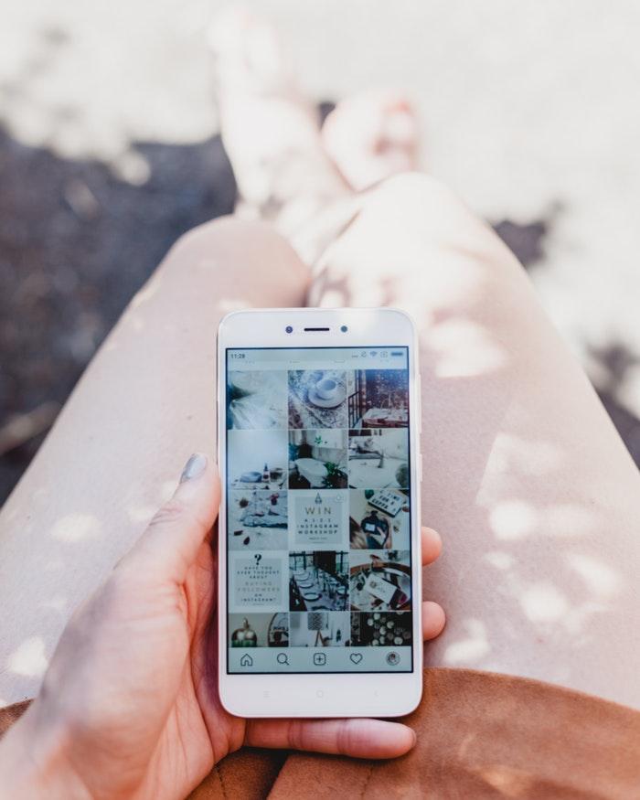 Kobieta trzymająca telefon na kolanach i przeglądająca instagram