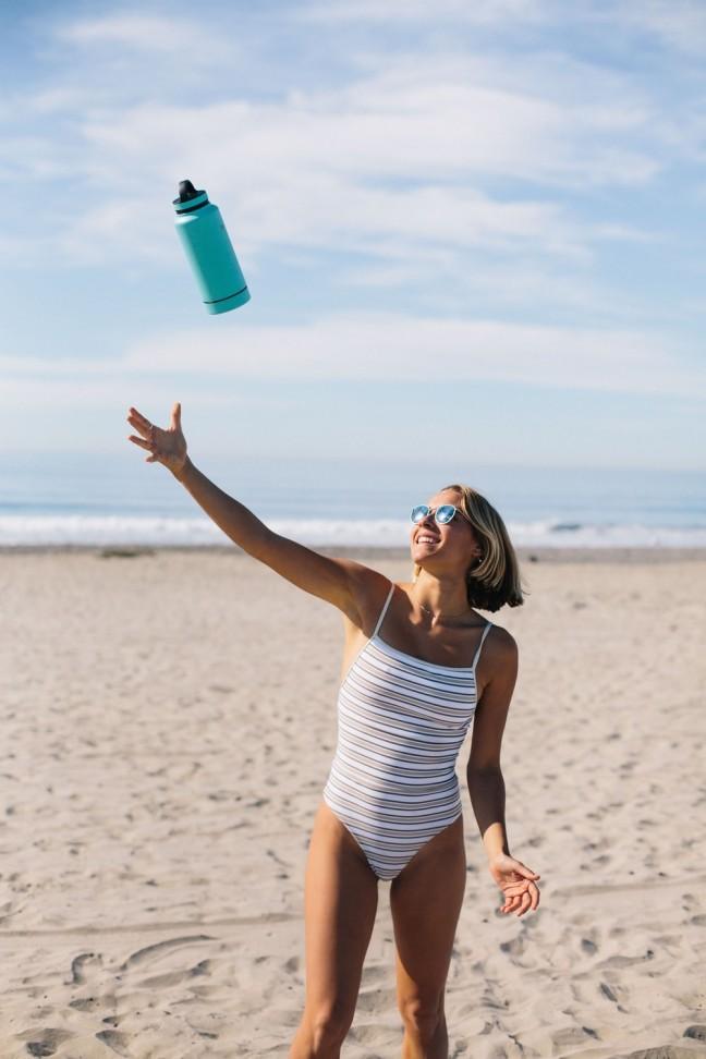 Kobieta łapiąca butelkę wody